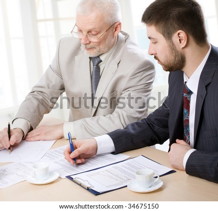 Three business people making notes - stock photo