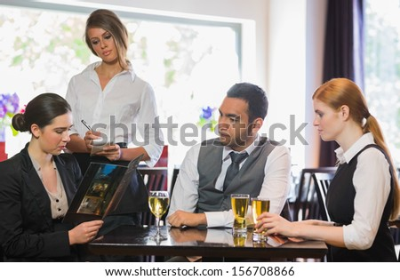 Three business people ordering a dinner in restaurant from waitress - stock photo
