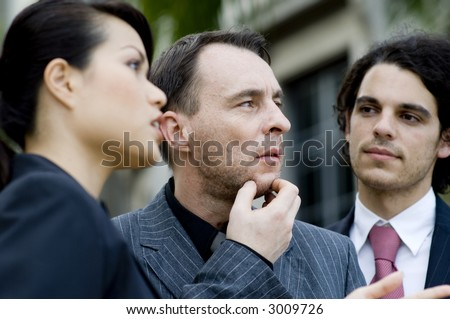 Three business people outside with the middle person thinking and in focus