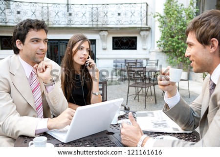Three business people sharing a table at a coffee shop terrace, having a meeting and using technology in the financial city district.