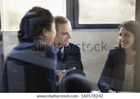 Three business people sitting and discussing at business meeting - stock photo