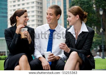 Three business people sitting outside having coffee break - stock photo