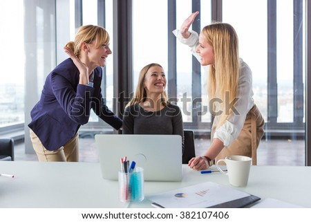 Three business women in modern office celebrating good project results. - stock photo