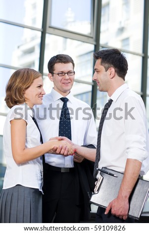 Three business workers communicating and handshaking in front of office building. Happy people trying to achieve the goal between their companies outdoors.