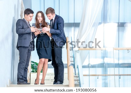 Three businessman standing on the stairs solve business problems. Several young people are at each other and smiling. People hold a tablet in the hands - stock photo