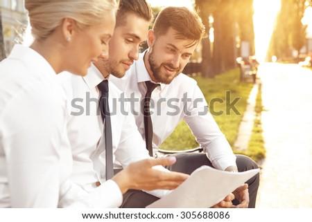 Three businessmen discussing sales figures - stock photo
