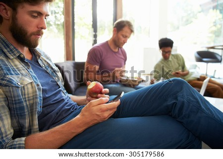 Three Businessmen Having Working Lunch In Office - stock photo