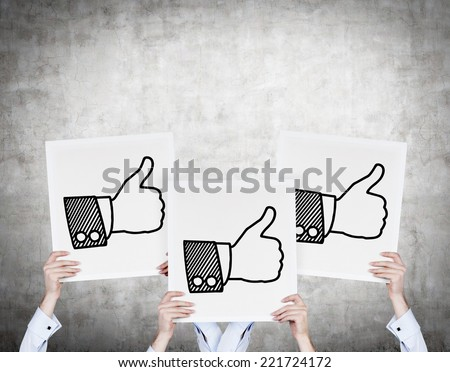 Three Businessmen hold an icon 'thumb up' of the successful transaction. - stock photo