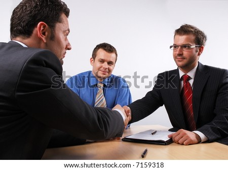 Three businessmen sitting at a table negotiating and signing a contract. handshake.