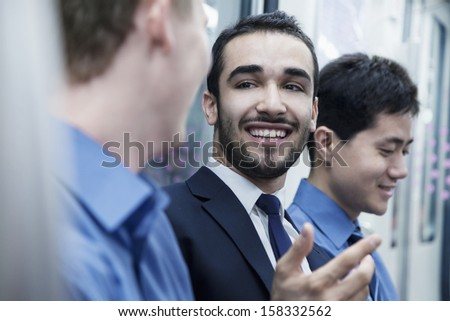 Three businessmen sitting in a row and talking on the subway - stock photo