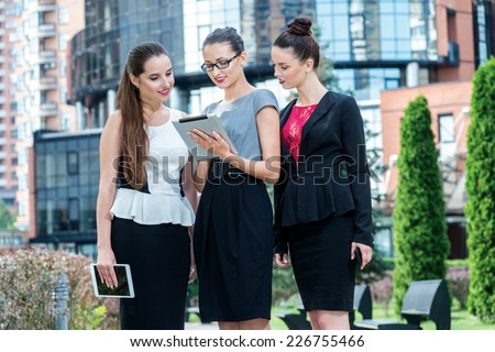 Three businessmen standing on the street. Three girls businessmen holding tablets and stand together.