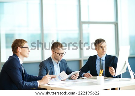 Three businessmen working together in office - stock photo