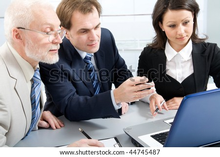 Three businesspeople discussing computer work