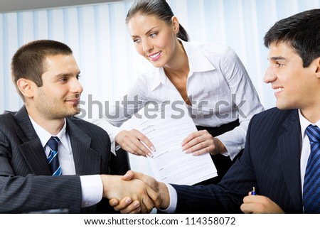 Three businesspeople handshaking with document at office - stock photo