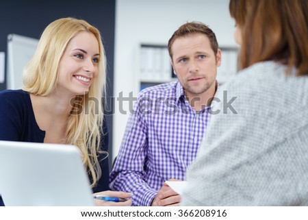 Three businesspeople in a meeting at the office having a discussion , low angle view past one colleagues shoulder to a pretty young businesswoman - stock photo