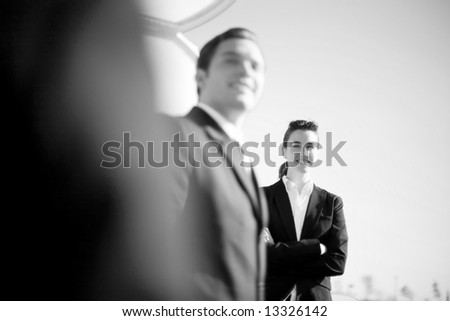 three businesspeople in a row with businesswoman standing looking at the camera with her arms crossed - stock photo