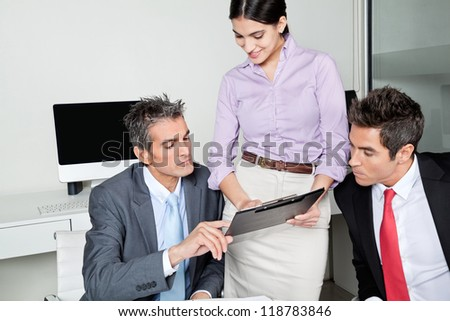 Three businesspeople in meeting at office - stock photo