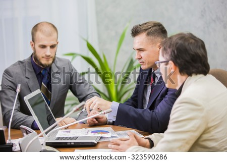 three businesspeople interacting at meeting