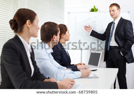 Three businesspeople listening to a teacher at the seminar