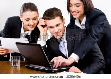 Three businesspeople looking at the screen of laptop with smiles with one of businesswomen pressing a key