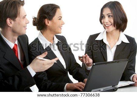 Three businesspeople sitting at table and discussing their work - stock photo