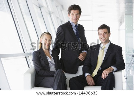 Three businesspeople sitting in office lobby smiling - stock photo