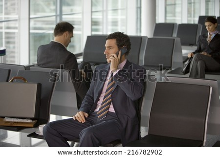 Three businesspeople sitting in the airport. - stock photo