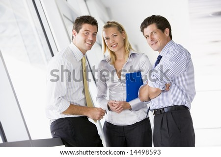Three businesspeople standing in corridor smiling - stock photo
