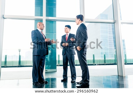 Three businesspeople standing in office lobby in front of city skyline