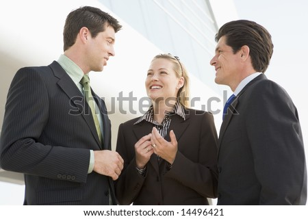 Three businesspeople standing outdoors by building talking and smiling - stock photo