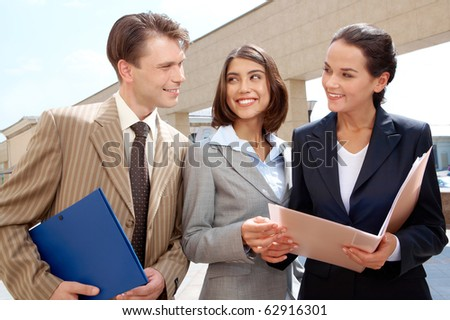 Three businesspeople standing outdoors with folders and talking - stock photo
