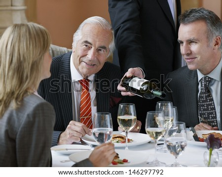 Three businesspeople talking at restaurant table as waiter serves wine - stock photo