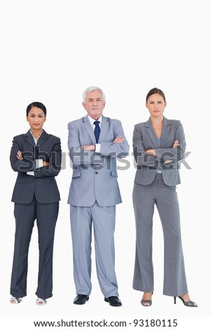 Three businesspeople with arms folded against a white background