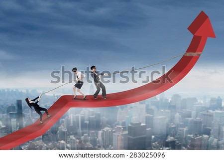 Three businesswoman try to climb and pulling arrow upward, shot above the city - stock photo