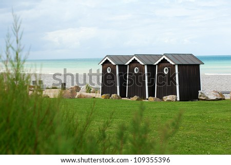 Three cabanas on a beach in Normandy, France