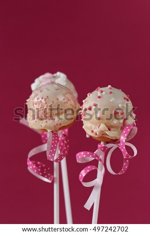 three Cake pops mixed  and a pink ribbon with white polka dots on a pink background