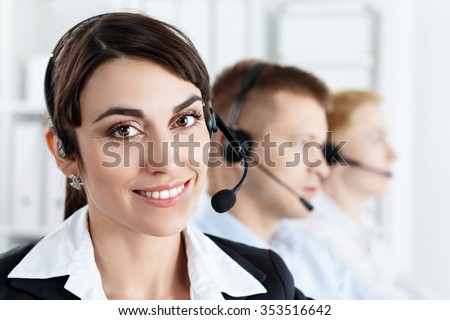 Three call centre service operators at work. Portrait of smiling pretty female helpdesk employee with headset at workplace. Effective and efficient business information, help and support concept