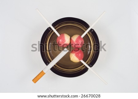 three candies and a cigarette figuring fight against smoking - stock photo