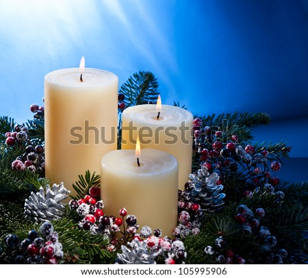 Three candles in an advent flower arrangement for advent and Christmas - stock photo