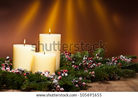 Three candles in an advent flower arrangement for advent and Christmas on a wooden surface