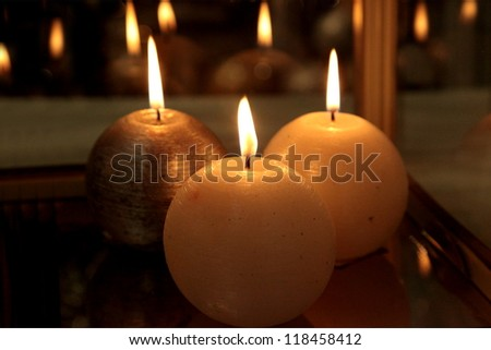 Three candles in the dark on a window sill
