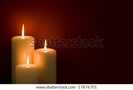 Three candles on a red background - stock photo