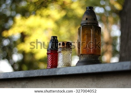 Three candles on an autumn cemetery - stock photo