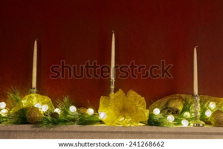 Three candlesticks on mantle with Christmas ornaments, lights, and ribbon - stock photo