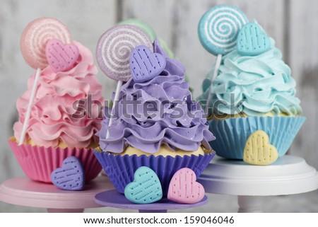 Three candy land lollipop cupcakes - stock photo