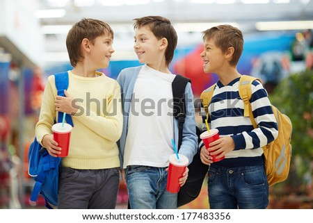Three carefree schoolboys talking after studies - stock photo