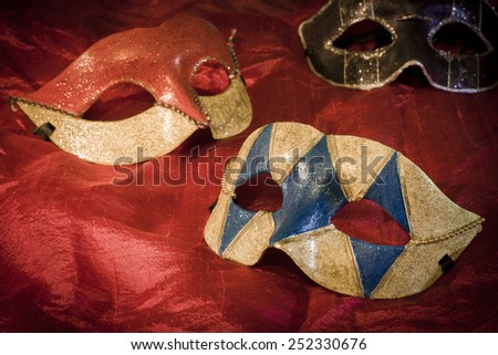 Three carnival masks on red background