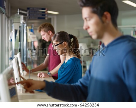 three caucasian students typing on touch screen computers in library, searching through database. Horizontal shape, side view, waist up - stock photo