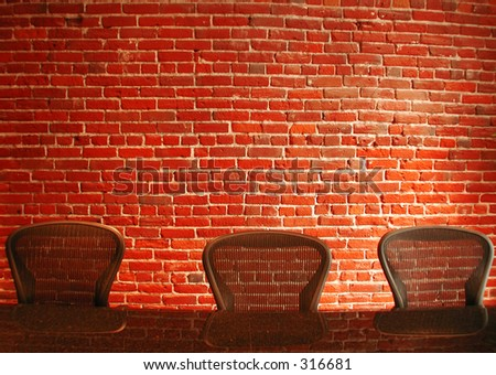 Three chairs and a brick wall