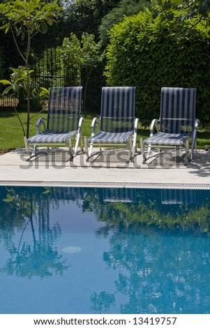 Three chairs by the pool